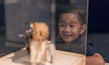 Young boy watching crafts indoors